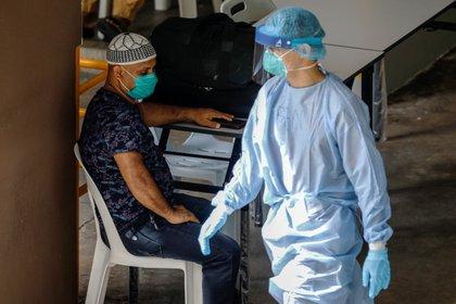 Personal médico atiende a personas afectadas por el COVID-19 en Singapur, April 28, 2020 (REUTERS/Edgar Su)