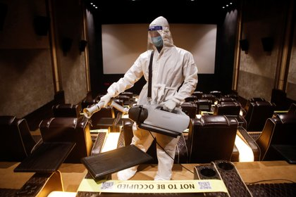 A man in personal protective equipment (PPE) sanitizes a cinema hall before a movie amid the spread of the coronavirus disease (COVID-19) in Mumbai, India November 15, 2020. REUTERS/Francis Mascarenhas