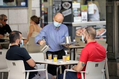Un camarero sirve el desayuno en la terraza de un bar en la región de Madrid (REUTERS/Javier Barbancho)