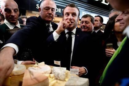 El presidente de Francia, Emmanuel Macron, come queso durante su visita a la 57ª Feria Internacional de Agricultura (Salon international de l'Agriculture) en el centro de exposiciones de la Porte de Versailles en París, el 22 de febrero de 2020. Ludovic Marin/Pool vía REUTERS