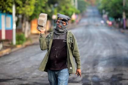 El miembro de una de las fuerzas de choque de Ortega carga una piedra en Monimbo en Masaya, (REUTERS/Oswaldo Rivas)