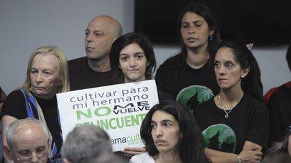 Valeria Salech (abajo) en 2016, junto a su hija Ariadna, que sostiene un cartel por la salud de su hermanito, en una audiencia en el Congreso (Télam)