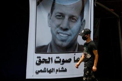 Un manifestante iraquí usa una máscara protectora cuando pasa junto a un póster que representa al ex asesor gubernamental y analista político Hisham al-Hashemi, quien fue asesinado por hombres armados, en la plaza Tahrir en Bagdad, Iraq, 8 de julio de 2020. (REUTERS / Thaier al-Sudani)