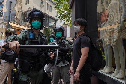 Policías antimotines forman una línea mientras identifican a peatones reunidos en el distrito Central de Hong Kong, el miércoles 27 de mayo de 2020. (AP Foto/Vincent Yu)