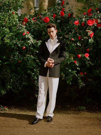 El actor Josh O'connor lució un esmoquin de saco negro con el distintivo de solapa blanca, camisa off white y pantalón negro. Completó el estilismo con zapatos de cuero negro (@goldenglobes)