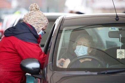 Una mujer recibe la vacuna COVID-19 en una unidad por un centro de vacunación, en medio del brote de la enfermedad por coronavirus (COVID-19), en Hyde, Gran Bretaña, el 7 de enero de 2021 (REUTERS / Molly Darlington)