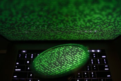 Un espejo refleja una pantalla de ordenador que muestra un código binario. EFE/RITCHIE B. TONGO/Archivo