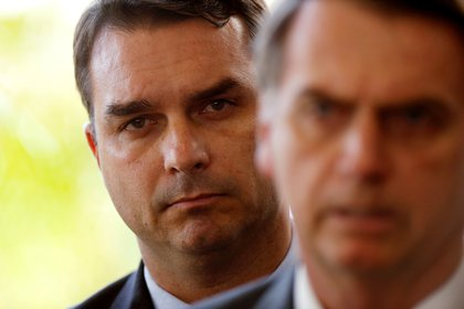 FILE PHOTO: Flavio Bolsonaro, son of Brazil's President Jair Bolsonaro, is seen behind him at the transition government building in Brasilia, Brazil November 27, 2018. REUTERS/Adriano Machado/File Photo