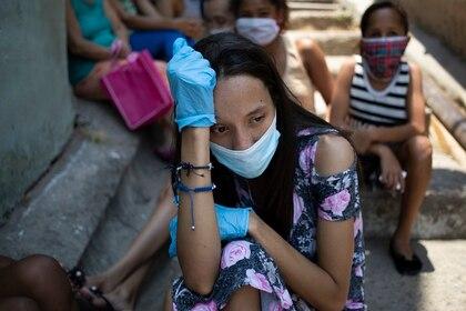Una mujer con mascarilla y guantes desechables para combatir el coronavirus espera ante un comedor social en la barriada de Petare, en Caracas, Venezuela, el jueves 30 de abril de 2020. (AP Foto/Ariana Cubillos)