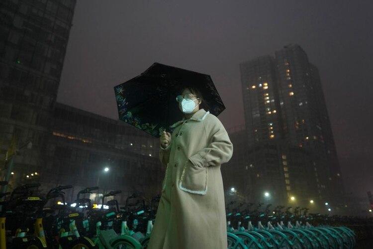 Una mujer con mascarilla sostiene un paraguas en medio de la lluvia mientras camina, en Pekín, China, el 29 de febrero de 2020. REUTERS/Stringer