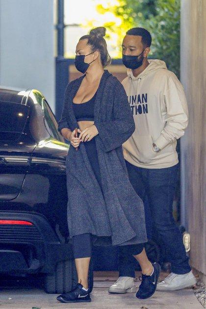 Chrissy Teigen y John Legend compartieron una noche con amigos en West Hollywood, California. La modelo lució un conjunto de top y calzas, zapatillas deportivas y un tapado largo, mientras que el cantante optó por un look casual: jean, buzo y zapatillas de cuero. Ambos usaron su tapabocas