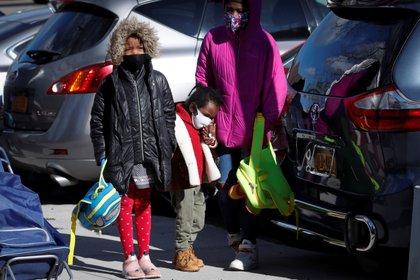 Niñas esperan en fila para recoger paquetes de comida gratis durante una operación de rescate de alimentos llevada a cabo por City Harvest durante el brote del COVID-19 en el distrito del Bronx de la ciudad de Nueva York el 22 de abril de 2020. REUTERS/Mike Segar