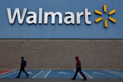 FILE PHOTO: Men walk past the logo of Walmart outside a store in Monterrey, Mexico February 12, 2018. REUTERS/Daniel Becerril/File Photo