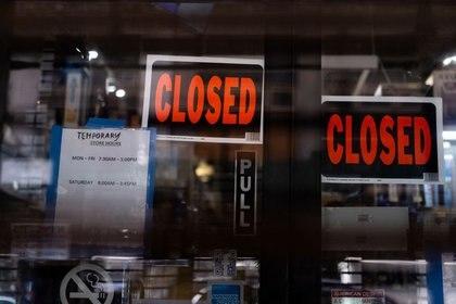 Se ve un cartel de cierre temporal en una tienda del distrito de Manhattan tras el brote de la enfermedad del coronavirus (COVID-19), en la ciudad de Nueva York, EEUU, el 15 de marzo de 2020. REUTERS/Jeenah Moon