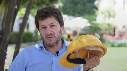 Andy, el voluntario e intérprete, mostrando el casco que usó en la AMIA