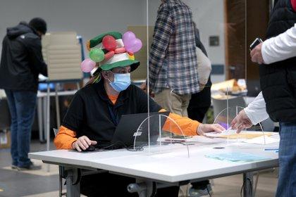 Una mujer disfrazada trabaja en un centro de voto anticipado en Virginia
