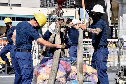 Dos tripulantes del cutter Hamilton mueven parte del cargamento de drogas incautado (USCG)