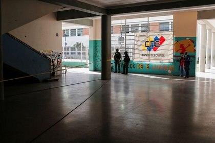 Miembros de la Guardia Nacional Bolivariana de Venezuela junto a una pancarta con el símbolo del Consejo Electoral de Venezuela en un colegio electoral durante las elecciones parlamentarias en Caracas, Venezuela, el 6 de diciembre de 2020. REUTERS / Manaure Quintero