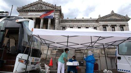 Trabajadores sanitarios realizando pruebas frente al Congreso uruguayo (Pablo PORCIUNCULA / AFP)