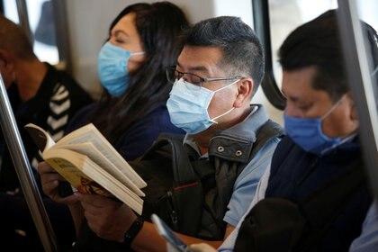 Un hombre con una máscara protectora lee un libro mientras viaja en el metro de la CDMX (Foto: Reuters)