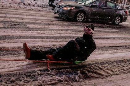 Un hombre es llevado en un trineo atado a un camión mientras la nieve sigue cayendo en Times Square (Scott Heins/Getty Images/AFP)