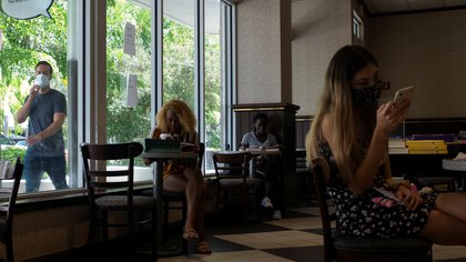 People have drinks at a Starbucks cafe inside a Barnes & Nobles bookstore, as Miami-Dade county allows indoor servicing in restaurants after easing some lockdown measures put in place during the coronavirus disease (COVID-19) outbreak, in Miami, Florida, U.S., August 31, 2020. REUTERS/Marco Bello