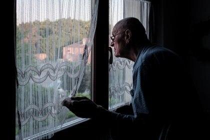 La vida en cuarentena: Gino Verani, de 87 años, mira por la ventana de su casa en San Fiorano, una de las ciudades originales de la 'zona roja' en el norte de Italia que ha estado cerrada desde febrero (Reuters)