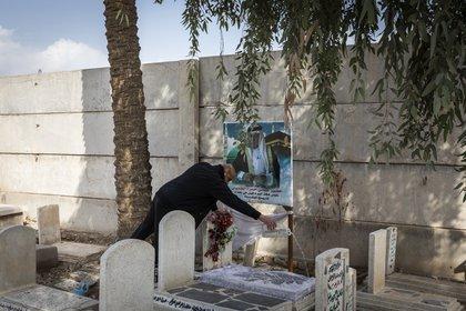Un doliente vierte agua de rosas para bendecir la tumba de su padre, que murió recientemente de COVID-19, en un cementerio frente al santuario del profeta bíblico Josué, en Bagdad, el 29 de enero de 2021. (Ivor Prickett/The New York Times).