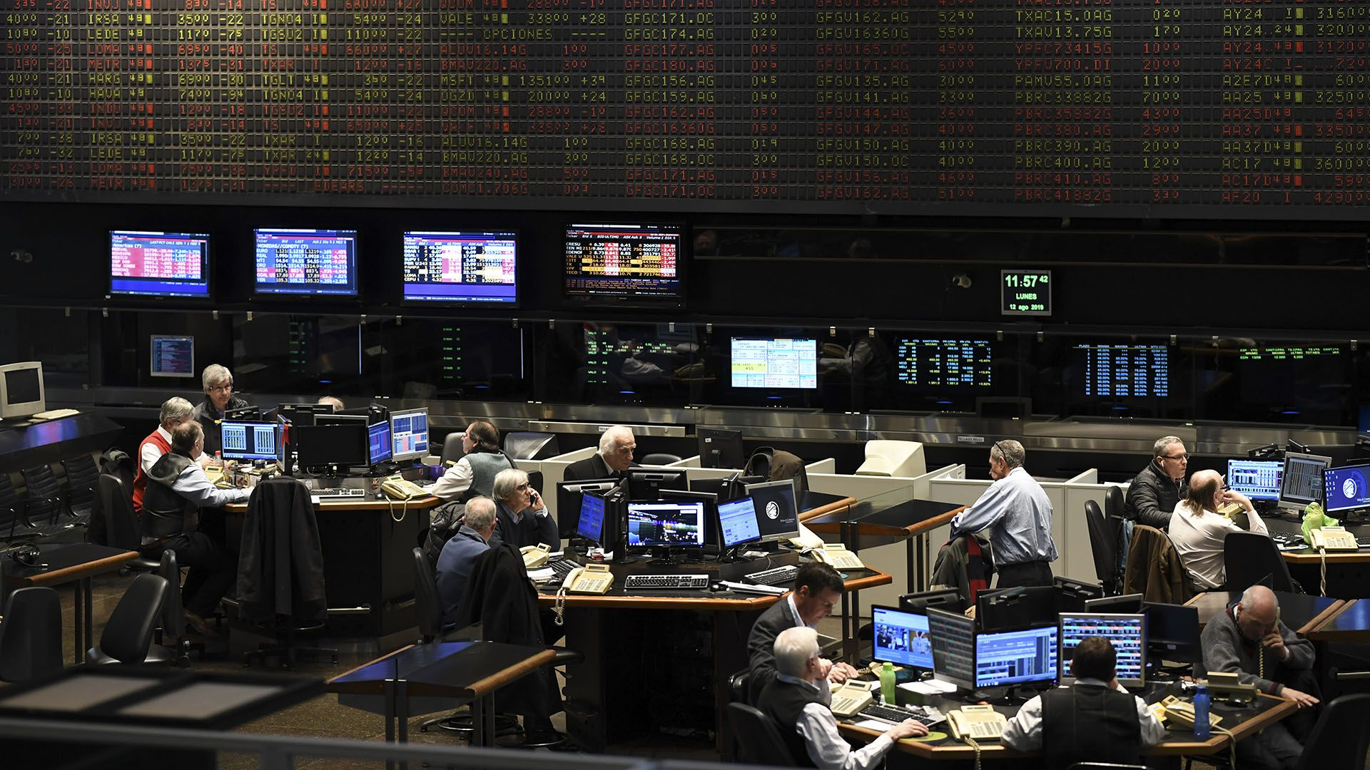 Traders are seen at the Stock Exchange in Buenos Aires on August 12, 2019. - The Buenos Aires stock exchange plunged 10 percent at the start of operations on Monday following liberal President Mauricio Macri's crushing defeat in party primaries over the weekend. Markets reacted with jitters to Macri's massive re-election blow as the peso also went into free fall against the dollar, dropping from 46.55 on Friday to 60. (Photo by RONALDO SCHEMIDT / AFP)
