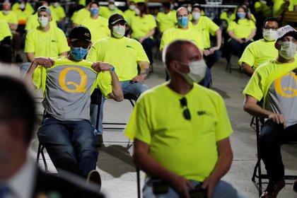 Empleados de la distribuidora de equipos médicos Owens & Minor con sombreros en apoyo al presidente de los Estados Unidos Donald Trump, levantan las camisetas de su compañía para revelar las camisetas debajo que apoyan el movimiento conspirativo de QAnon , el 14 de mayo de 2020 (REUTERS/Carlos Barria)