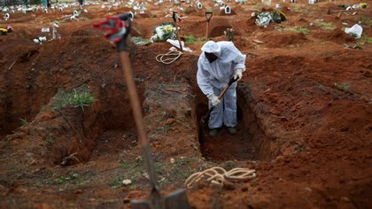 A gravedigger wearing a protective suit digs a grave to bury the coffin of a person who died from the coronavirus disease (COVID-19), at Vila Formosa cemetery, in Sao Paulo, Brazil, July 16, 2020. REUTERS/Amanda Perobelli