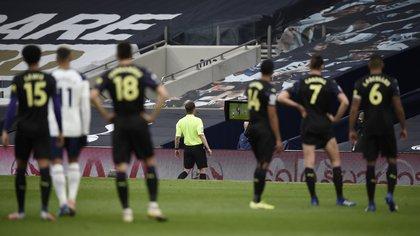 Los futbolistas de Tottenham y Newcastle aguardan con paciencia la resolución del árbitro, quien consulta una acción en la pantalla del VAR (REUTERS/Daniel Leal-Olivas)