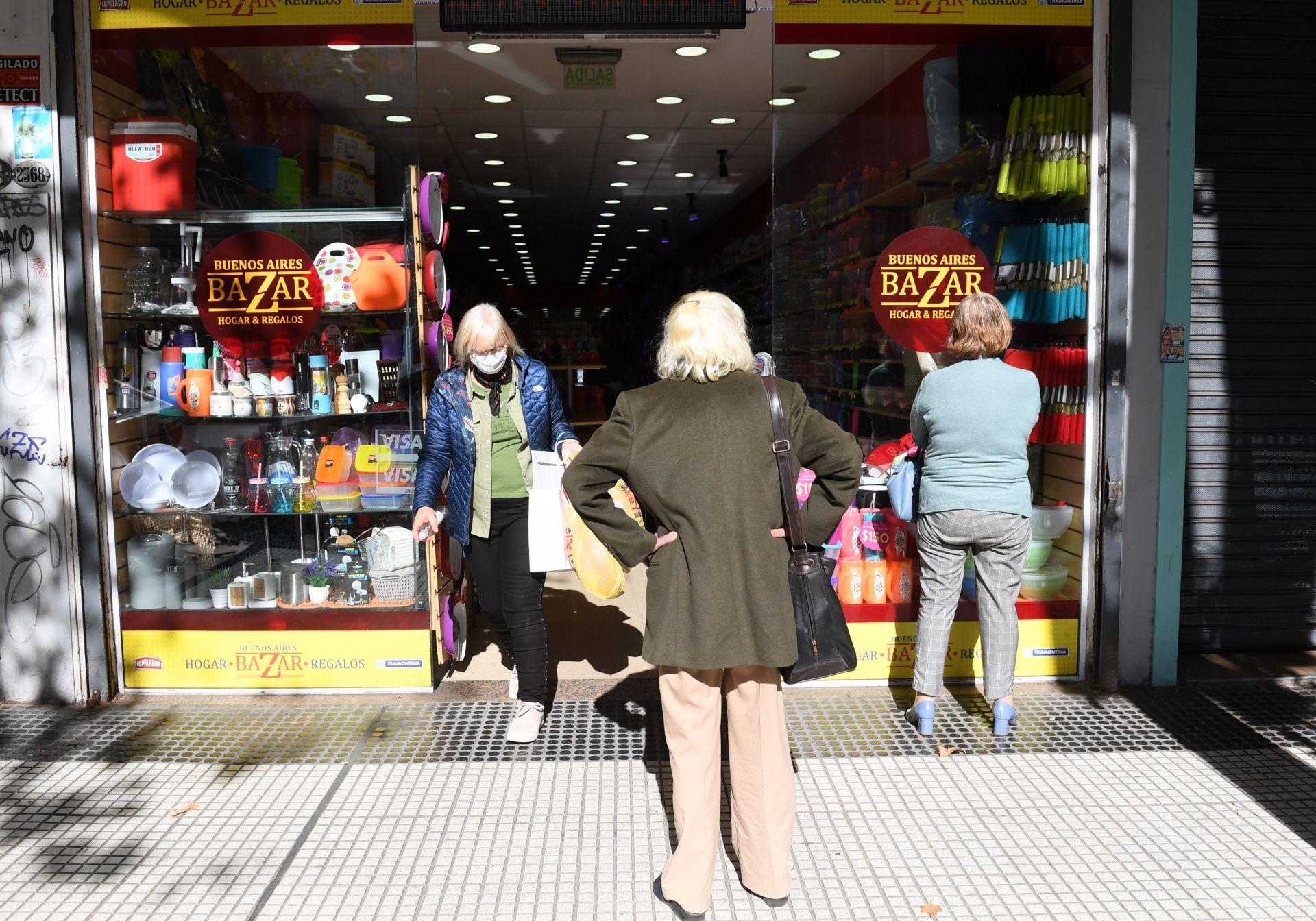 Tres mujeres hace fila para ingresar a un bazar, uno de los rubros que también reabrió sus puertas para la atención al público