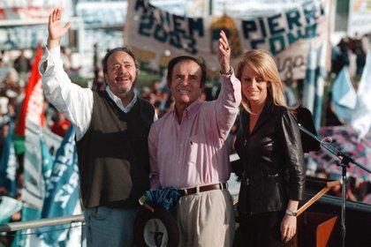 Carlos Menem, junto a su esposa Cecilia Bolocco, y Alberto Pierri, saludan luego del acto procelitista en el estadio de Laferrere ( NA:Mariano Sanchez)