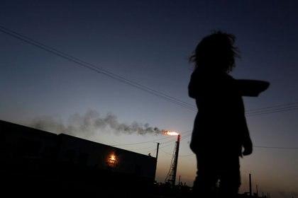FOTO DE ARCHIVO: Una niña se para frente a su casa mientras la refinería Cardón, que pertenece a la petrolera estatal venezolana PDVSA, es vista al fondo, en Punto Fijo, Venezuela, foto tomada el 22 de 2016. REUTERS/Carlos Jasso