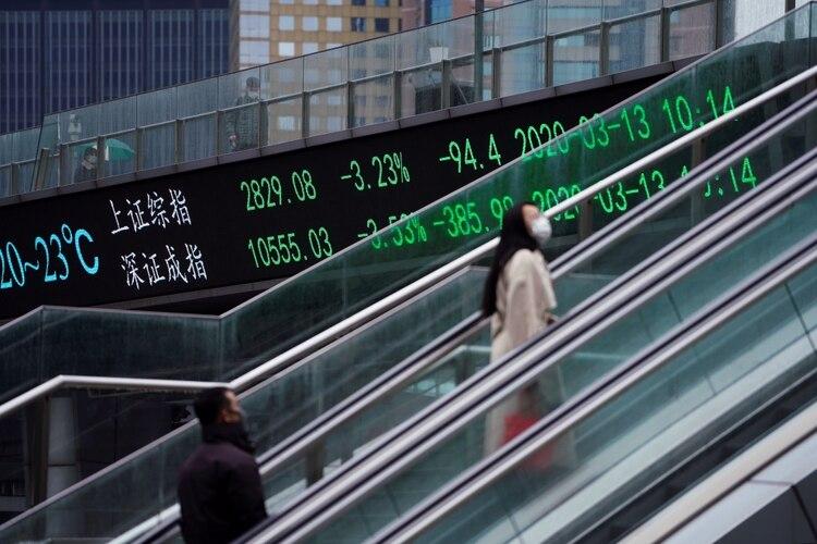 Persona que usa mascarilla para protegerse del coronavirus, sube esclareas mecánicas cerca de una pantalla digital con datos de la bolsa de Shangai