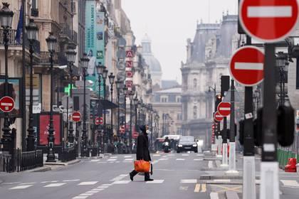 Un hombre con una máscara protectora cruza la desierta Rue de Rivoli en París el 18 de marzo de 2020 (REUTERS/Christian Hartmann)