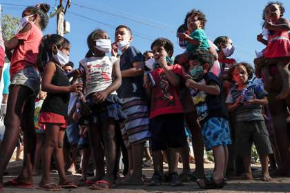 Fotografía fechada el 31 de mayo de 2020 de decenas de niños con tapabocas haciendo fila para recibir una donación de alimentos en la comunidad de Capadócia, en Brasilandia, un barrio en la periferia de la ciudad de São Paulo (Brasil). EFE/Sebastião Moreira