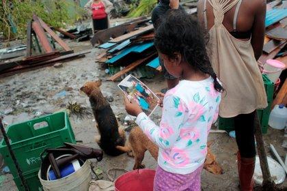 Una niña mira una fotografía en medio de un panorama desolador (REUTERS/Oswaldo Rivas)