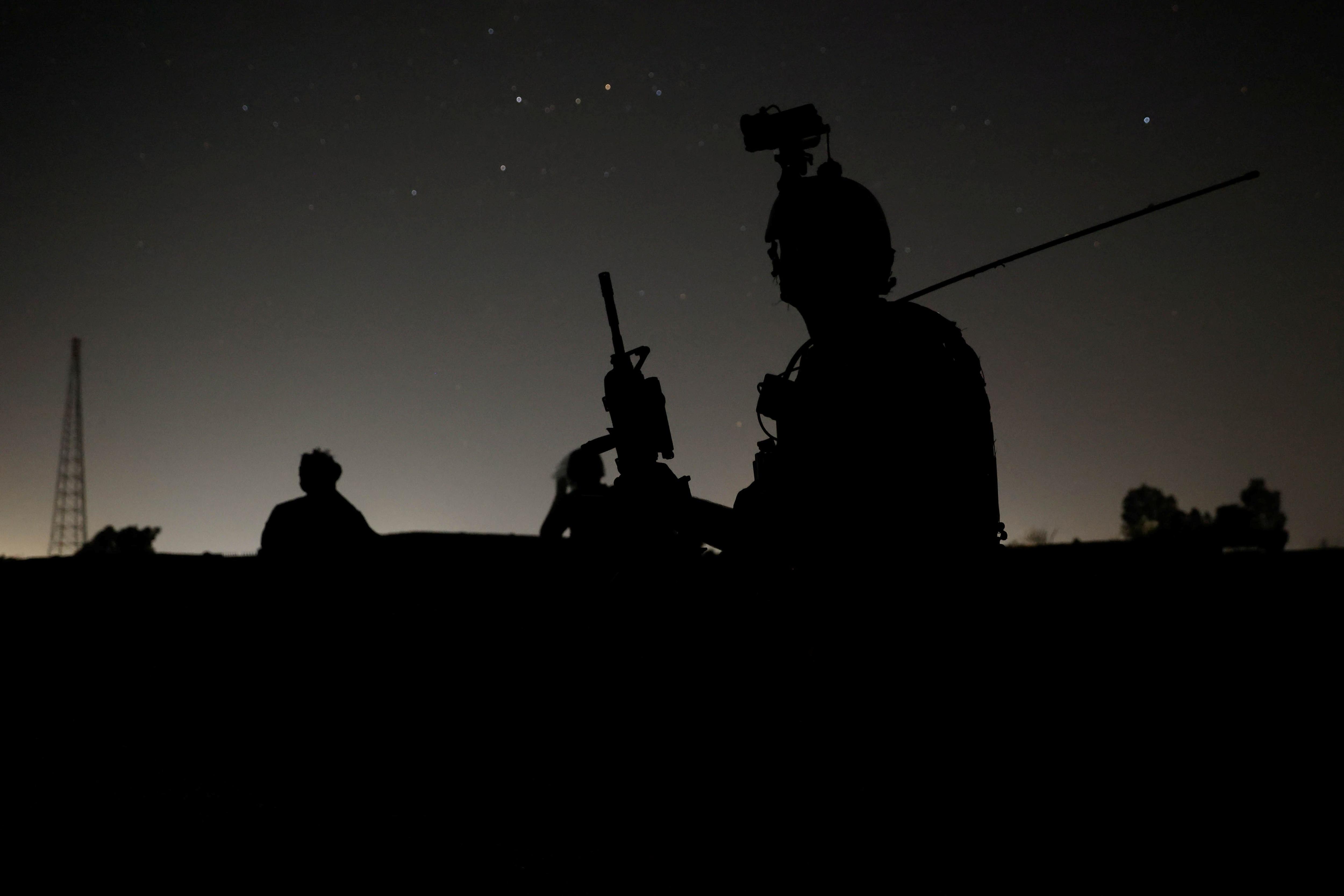 Miembros de las fuerzas especiales afganas vigilan mientras otros registran casas en un pueblo durante una misión de combate contra los talibanes, en la provincia de Kandahar, Afganistán, el 12 de julio de 2021. Foto tomada el 12 de julio de 2021.