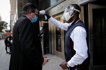 Un empleado toma la temperatura de un ejecutivo fuera del edificio Empire State de Nueva York, que se alista para reabrir la mayoría de sus negocios y empresas. Junio, 2020. REUTERS/Mike Segar