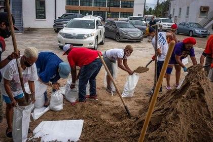 Residentes de New Orleans trabajan en equipo para armar sacos de arena contra las inundaciones (REUTERS/Kathleen Flynn)