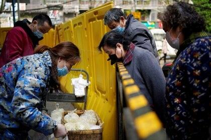 Residentes con máscaras compran a través de vallas amarillas que todavía bloqueaban en estos últimos días algunos bloques de apartamentos en Wuhan.