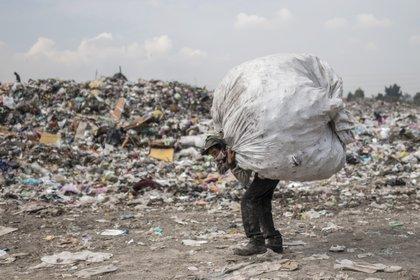 """Un recolector lleva una bolsa en el basurero """"Bordo de Xochiaca"""" en Ciudad Nezahualcóyotl, Estado de México el 21 de julio de 2020, en medio de la nueva pandemia de coronavirus. (Foto por PEDRO PARDO / AFP)"""