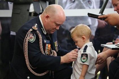 Un comisionado entrega una medalla póstuma a la valentía y servicio al hijo del bombero voluntario Geoffrey Keaton, quien murió luchando contra el fuego (Reuters)