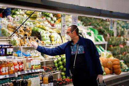 Un hombre con barbijo compra en un supermercado mientras los habitantes comienzan a acopiar alimentos tras el brote de coronavirus, en Buenos Aires, Argentina, el 15 de marzo de 2020. REUTERS/Agustin Marcarian