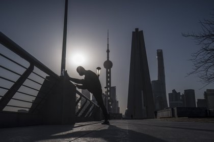 A man stretches on the Bund as skyscrapers of the Pudong Lujiazui Financial District stand across the Huangpu River during sunrise in Shanghai, China, on Friday, March 20, 2020. Most of China is now considered low risk and should return to normal work and life, Premier Li Keqiang said at a government meeting on the coronavirus, which is spreading rapidly in Europe, the U.S. and elsewhere. Photographer: Qilai Shen/Bloomberg
