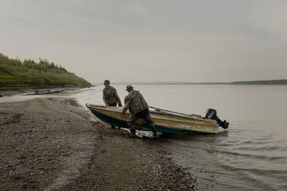 Pescadores sacando un bote del río Kolimá, al noreste de Sajá, cerca de las nueve de la noche. En el verano, el sol nunca se oculta por completo en esa región. (Emile Ducke/The New York Times)