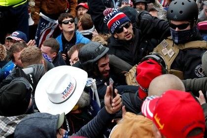 Un policía es rodeado por la multitud en las afueras del Capitolio (Reuters)
