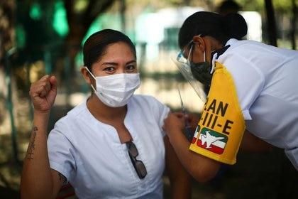 Una miembro del personal médico hace un gesto mientras recibe la primera inyección de la vacuna contra COVID-19 de Pfizer/BioNtech, en Ciudad de México, México, el 27 de diciembre de 2020. REUTERS/Edgard Garrido